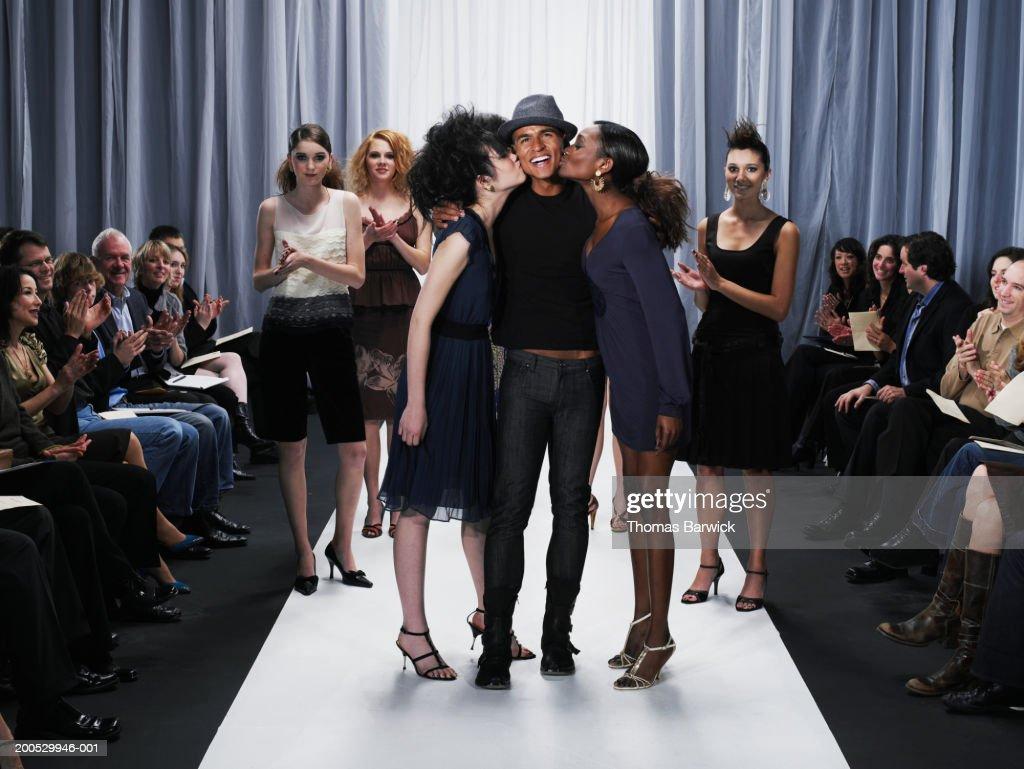 Female models kissing designer on cheek on catwalk : Stock Photo