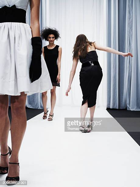 Female models walking down catwalk, one woman breaking high heel