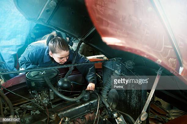 Female motor mechanic working on a car engine.