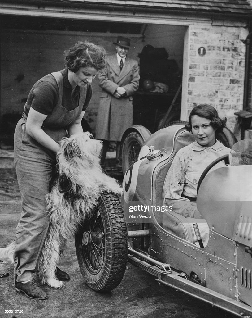 Female motor racing driver Kay Petre at the wheel of an Austin car as she is introduced by Mr A C Dobson to her pet dog during driving practice at...