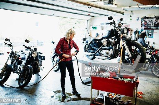 Female Motorcycle Mechanic Working In Garage Stock Photo