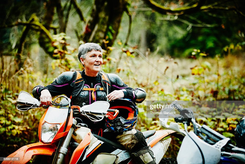 Female motorcyclist in discussion with friends after riding dirt bikes : Stock Photo