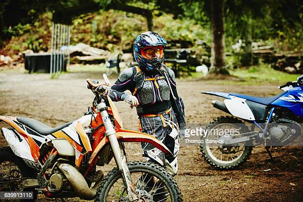 Female motorcyclist in helmet and protective gear standing next to dirt bike after ride