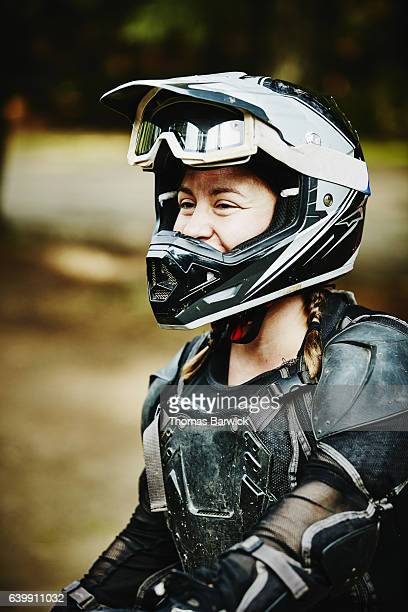 Female motorcyclist laughing after riding dirt bikes with friends