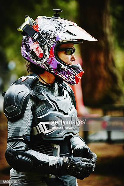 Female motorcyclist preparing for dirt bike ride with friends