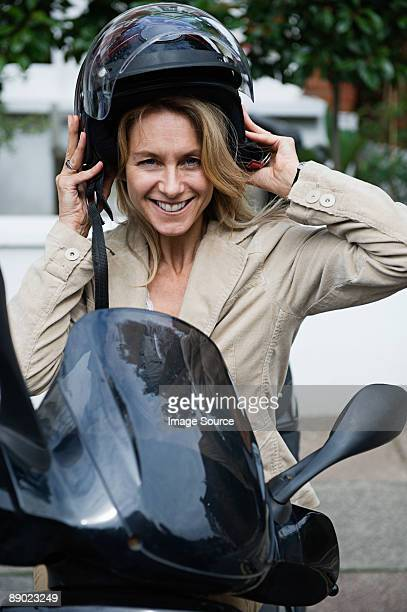 Female motorcyclist removing her helmet