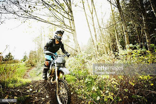 Female motorcyclist riding dirt bike on forest trail