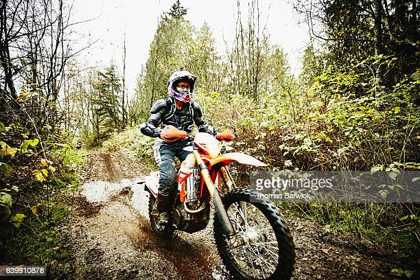 Female motorcyclist riding dirt bike on muddy forest trail