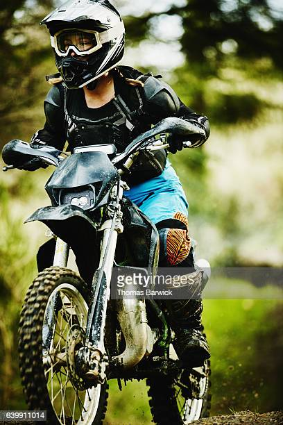 Female motorcyclist riding dirt bike on trail in forest
