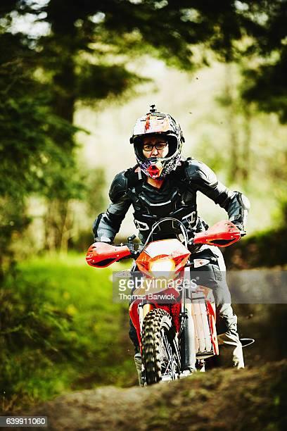 Female motorcyclist riding dirt bike on trail