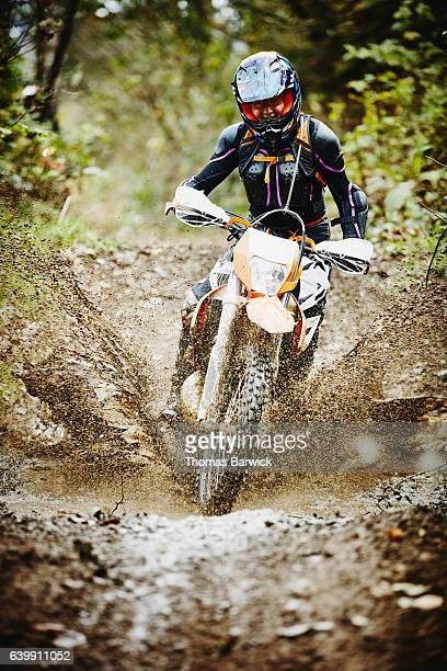 Female motorcyclist riding dirt bike though mud