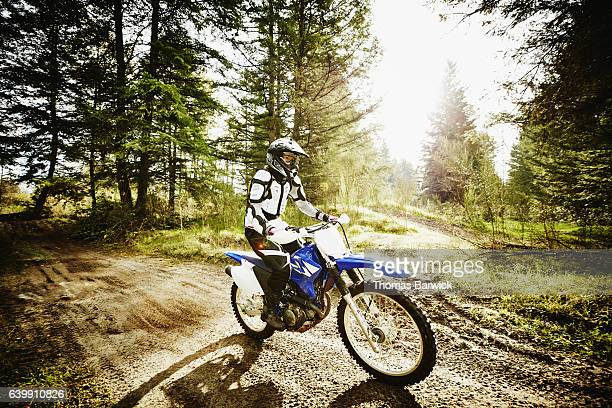 Female motorcyclist riding dirt bike through forest on sunny afternoon
