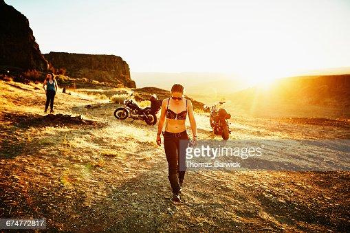 Female motorcyclist walking through camp at sunset