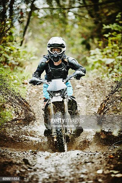 Female motorcyclists riding dirt bike though mud on forest trail