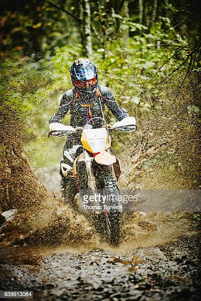 Female motorcyclists riding dirt bike though mud on trail