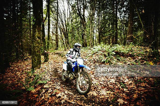 Female motorcyclists riding dirt bike through forest trail on fall afternoon
