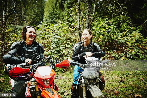 Female motorcyclists sitting on dirt bikes laughing after ride