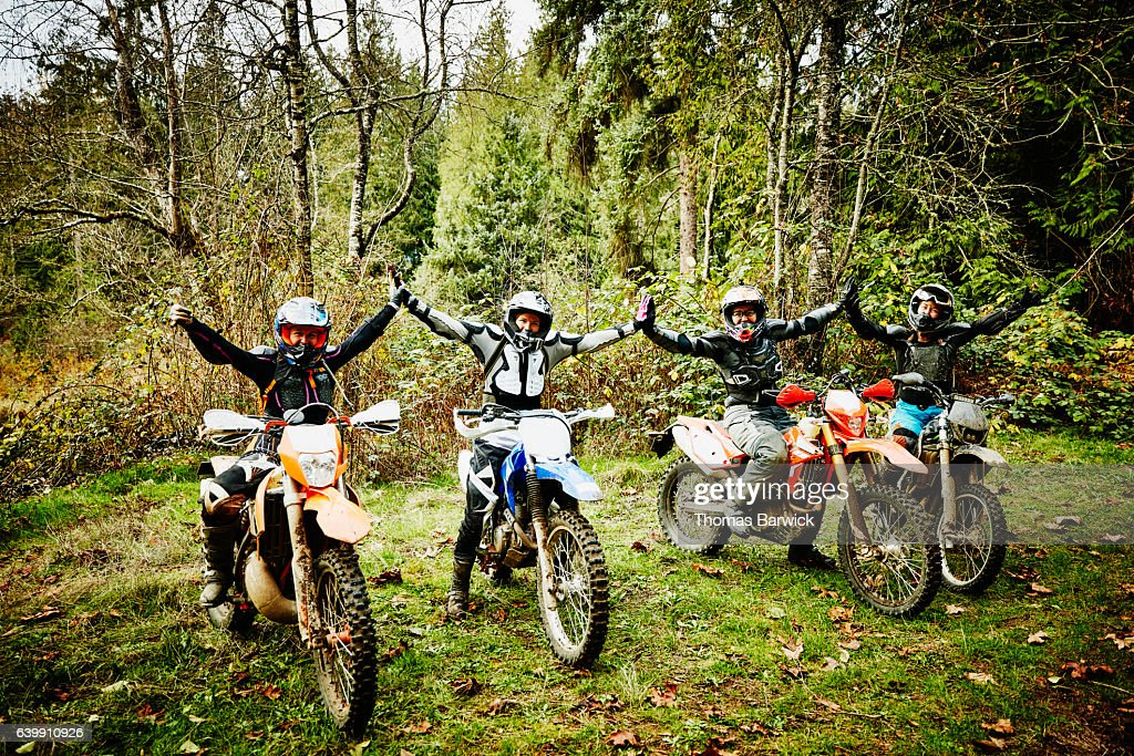 Female motorcyclists with arms raised together after riding dirt bikes