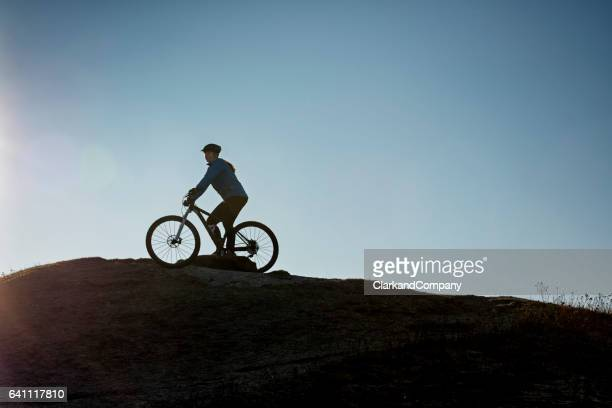 Female Mountain Bike Rider Silhouetted Against The Sky
