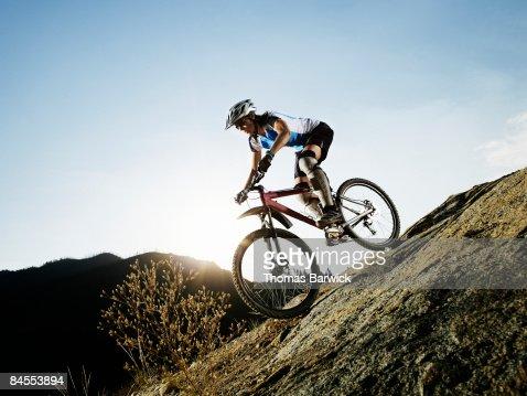 Female mountain biker descending on trail