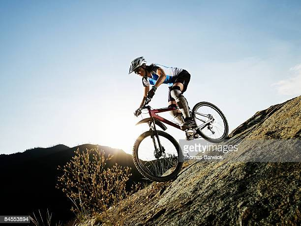 Female mountain biker descending on trail