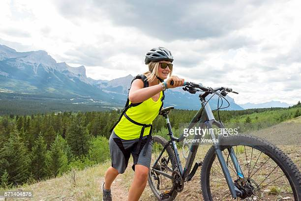 Female mountain biker pushes bike upslope