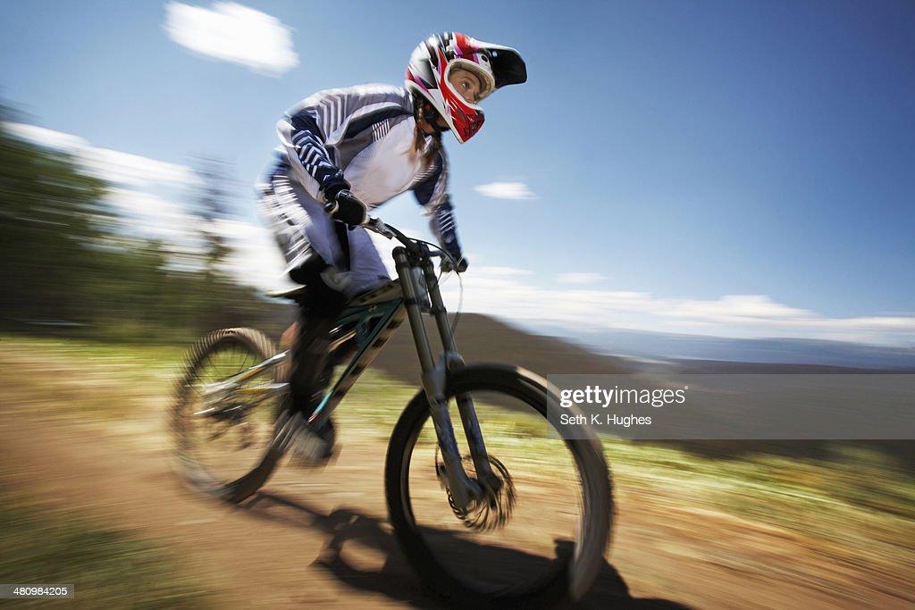 Female mountain biker speeding down dirt track : Stock Photo