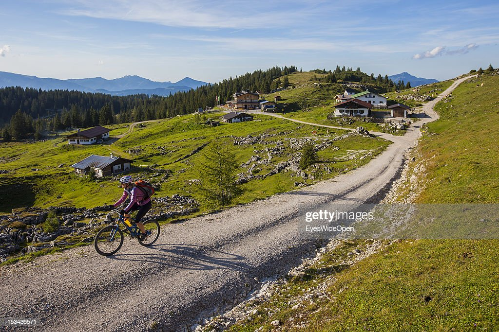 A female mountainbiker, a woman is cylcling uphill to the alpine mountain hut Straubinger Haus at the mountain of Fellhorn in the Bavarian Alps on August 29, 2012 in Reit im Winkl, Bavaria, Germany.
