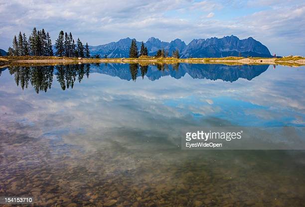 A female mountainbiker at the mountain lake Seidlalm See and the mountains and landscape of Wilder Kaiser in the tyrolean alps on October 05 2012 in...