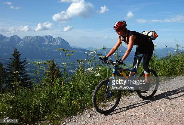 A female mountainbiker cycling down the Hahnenkamm with a view on the Kaisergebirge on August 16 2009 in Kitzbuhel Austria Kitzbuehel is famous for...