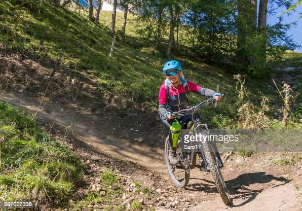 Female mountainbiker is riding downhill in hairpin turn in the Dolomites, Italy