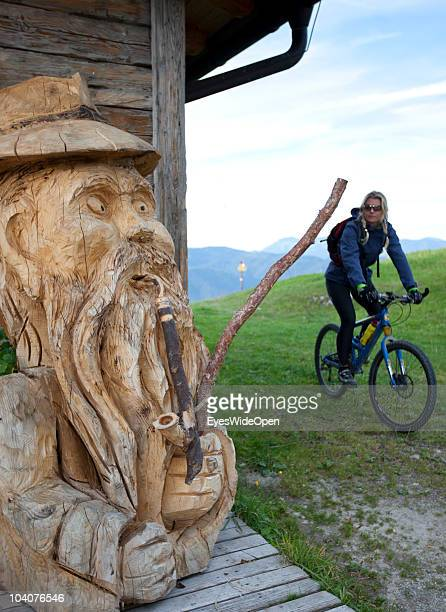 A female mountainbiker passing a hut with a woodcarving at Unterberg mountain on September 12 2010 in Koessen Austria