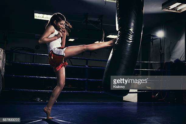Female muay thai fighter training with a punching bag