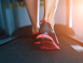 Female muscular feet in sneakers running on the treadmill at the gym. Concept for fitness, exercising and healthy lifestyle