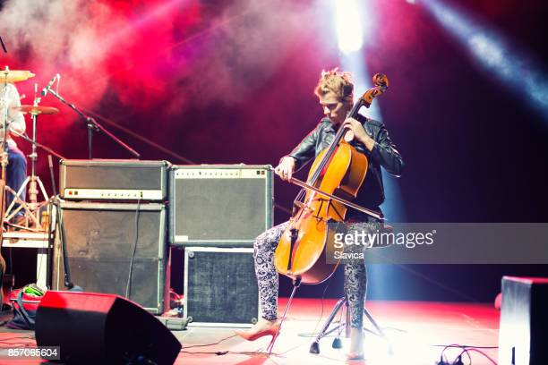 Female musician playing cello on stage under spotlights