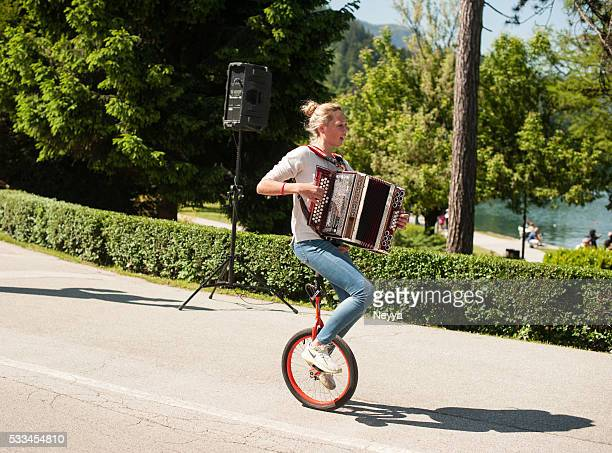 Female musician riding unicycle
