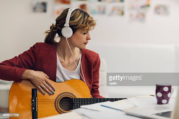 Female Musician Working In Her Home Recording Studio.