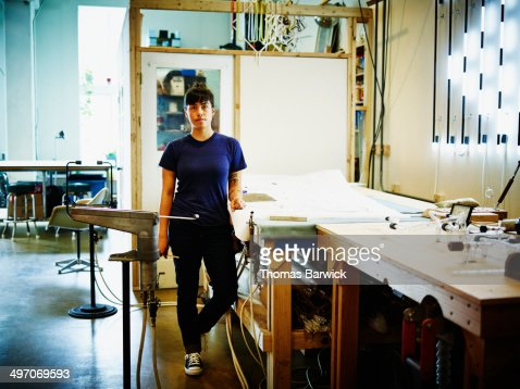 Female neon artist standing at work table