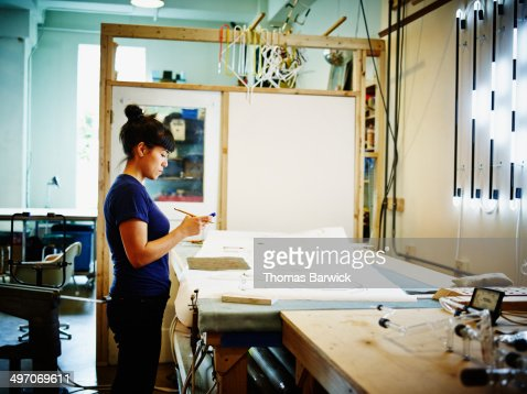 Female neon artist working on smart phone in loft