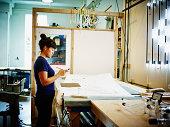 Female neon artist working on smart phone in loft