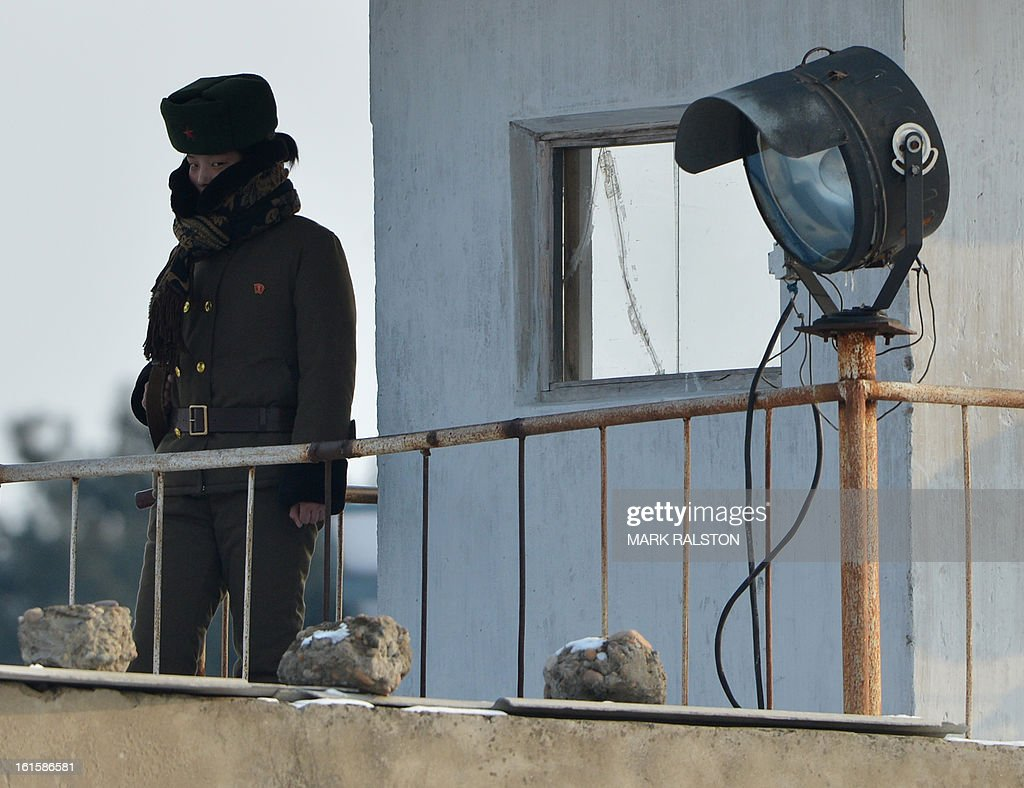 A female North Korean soldier is seen beside the Yalu River near the North Korean town of Sinuiju after the country conducted it's third nuclear test on February 12, 2013 across from the Chinese city of Dandong. North Korea staged its most powerful nuclear test yet on February 12, claiming a breakthrough with a 'miniaturised' device in a striking act of defiance to global powers including its sole patron China. AFP PHOTO/Mark RALSTON