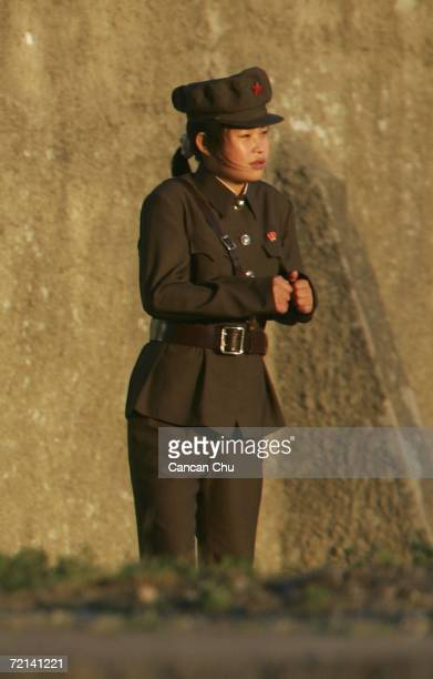 A female North Korean soldier suffers in the cold wind as she stands guard at a barback in the North Korean town of Sinuiju opposite the Chinese...