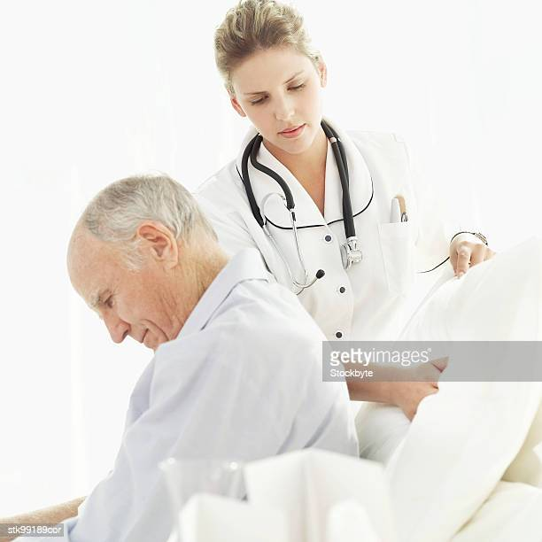 female nurse adjusting an elderly male patient's pillows