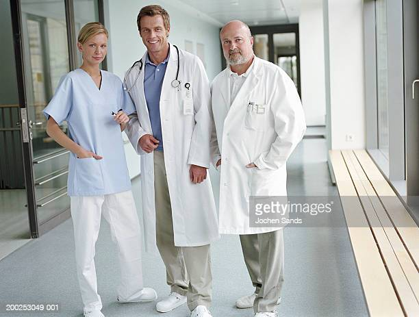 Female nurse and two male doctors in corridor, smiling, portrait