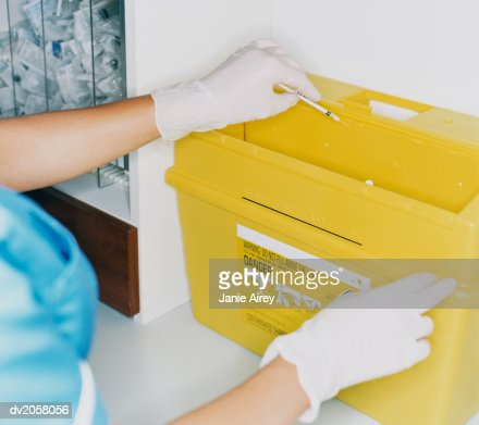 Female Nurse Disposing of a Syringe in a Waste Box