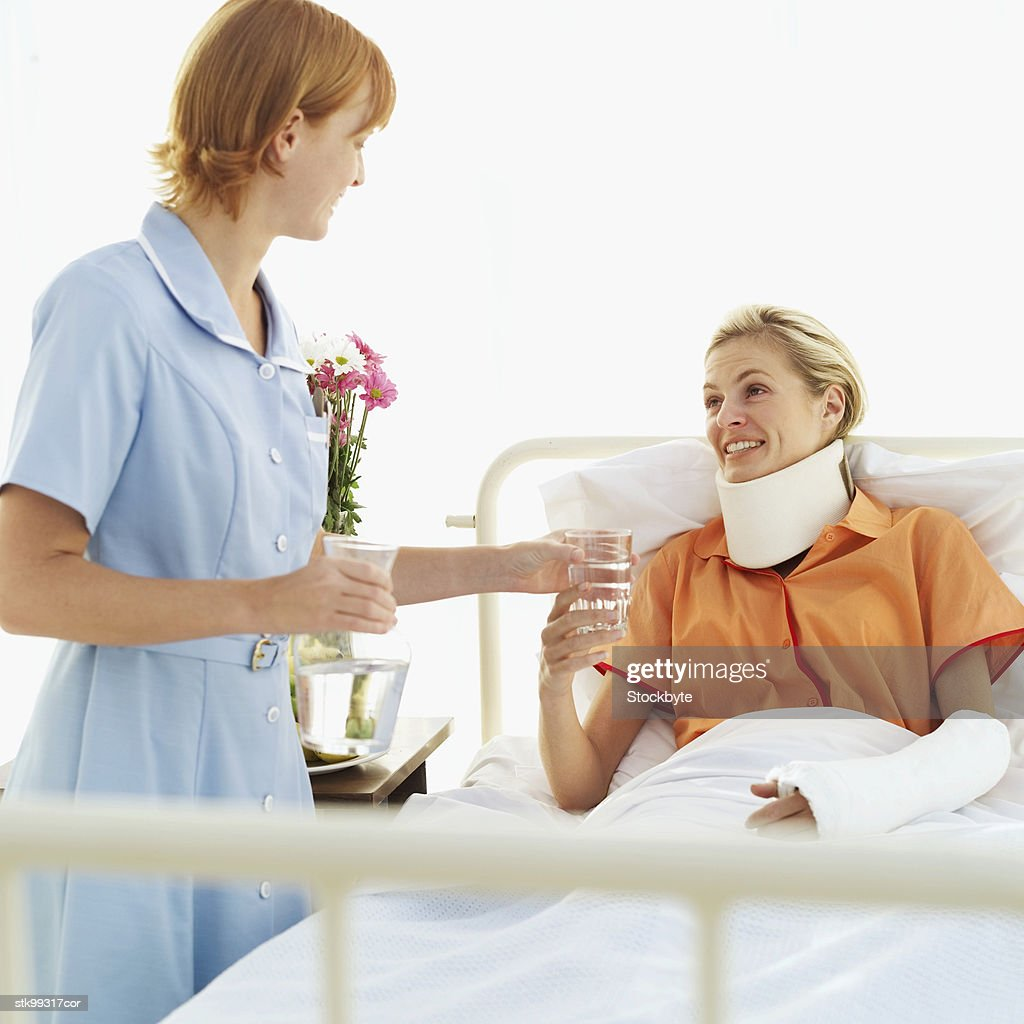 female nurse giving a glass of water to a woman wearing a neck brace and an arm cast : Stock Photo