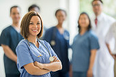A multi-ethnic group of doctors and nurses are standing together inside of the hospital. A female nurse is smiling and looking at the camera.