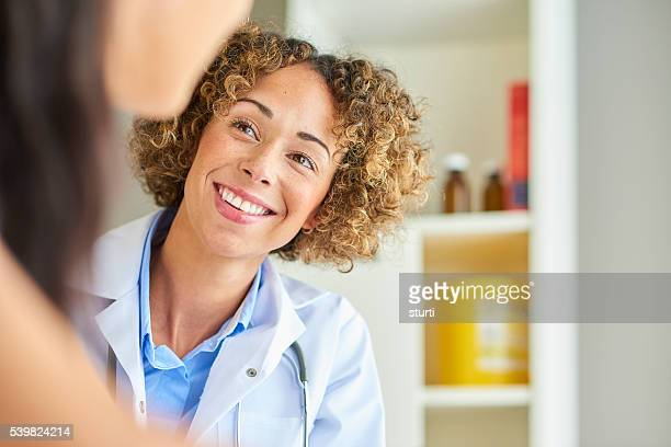 female nurse happily chatting to patient .