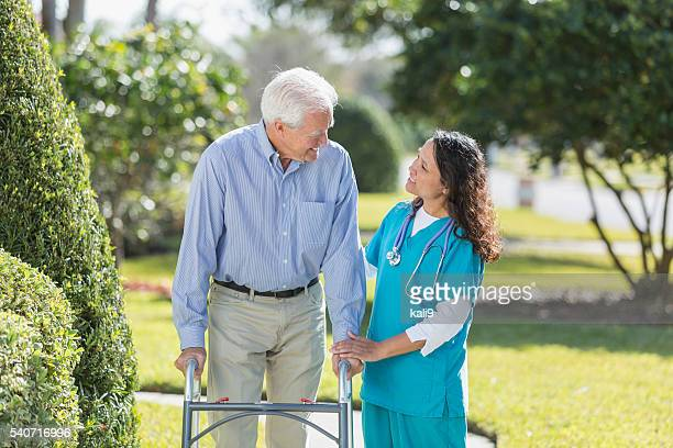 Female nurse helping senior man using walker outdoors