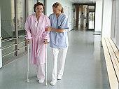Female nurse holding patient using crutches in hospital corridor
